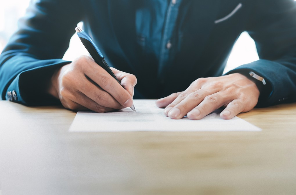 quebra de contrato na pandemia - homem assinando contrato